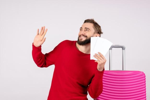 Vooraanzicht jonge man met roze tas en vliegtuigtickets op witte muur reis vlucht vakantie emotie foto toerist