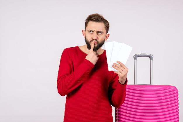Vooraanzicht jonge man met roze tas en vliegtuigtickets op witte muur te houden reisvluchten vakantie emotie foto toerist