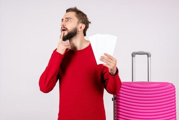 Vooraanzicht jonge man met roze tas en vliegtuigtickets op witte muur vlucht reis vakantie emotie foto toerist te houden