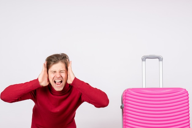 Vooraanzicht jonge man met roze zak schreeuwen op een witte achtergrond emotie model reis vlucht zomerkleur vakantie
