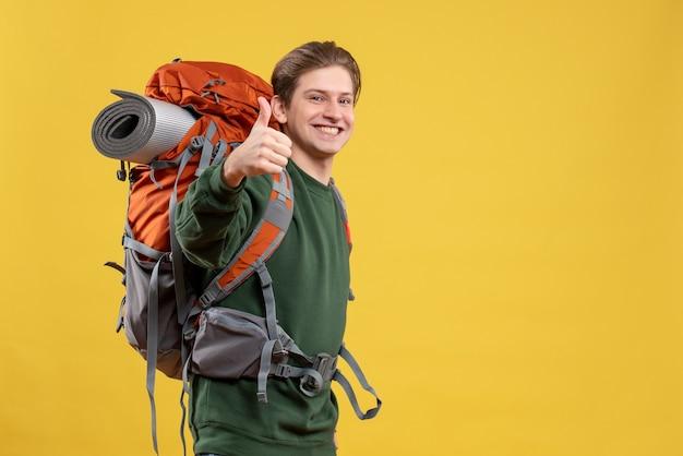 Vooraanzicht jonge man met rugzak die zich voorbereidt op wandelen glimlachend
