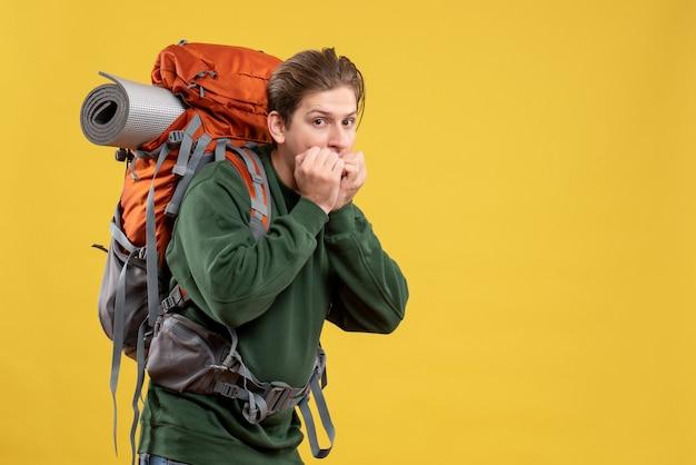 Vooraanzicht jonge man met rugzak die zich voorbereidt op wandelen met een bang gezicht