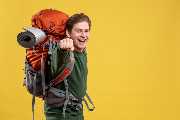 Vooraanzicht jonge man met rugzak die zich voorbereidt op wandelen opgewonden