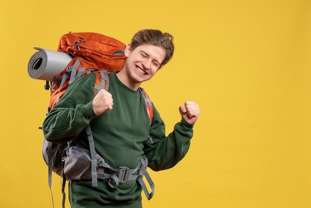 Vooraanzicht jonge man met rugzak die zich voorbereidt op wandelen