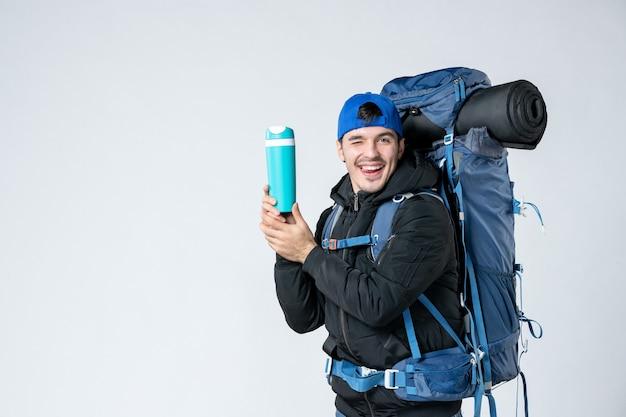Vooraanzicht jonge man met rugzak en thermos op witte achtergrond sneeuw bos natuur koude lucht tent kamp campagne