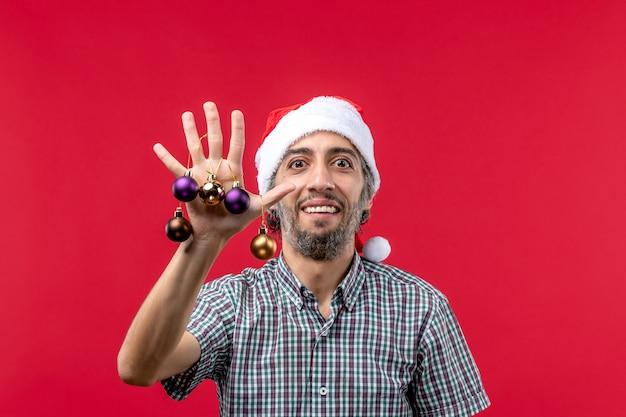 Vooraanzicht jonge man met schattig plastic speelgoed op de rode achtergrond
