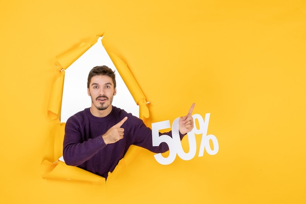 Vooraanzicht jonge man met schrijven op gele achtergrond foto's vakantie cadeau verkoop kleur xmas shopping