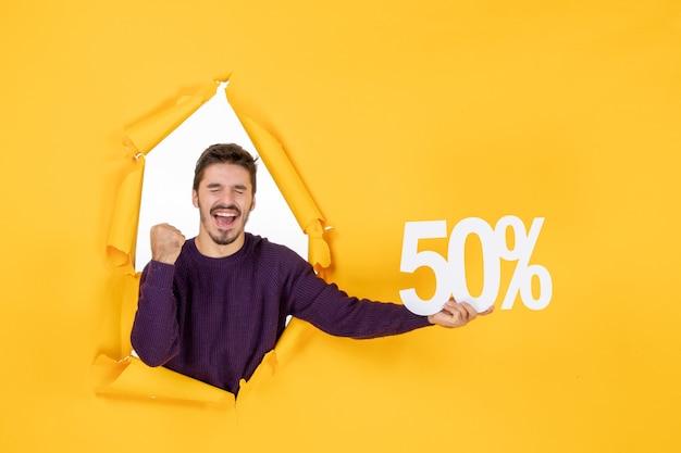 Vooraanzicht jonge man met schrijven op gele achtergrond winkelen vakantie xmas kleur cadeau sale nieuwjaar