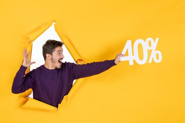 Vooraanzicht jonge man met schrijven op gele achtergrond winkelen xmas gift foto kleur