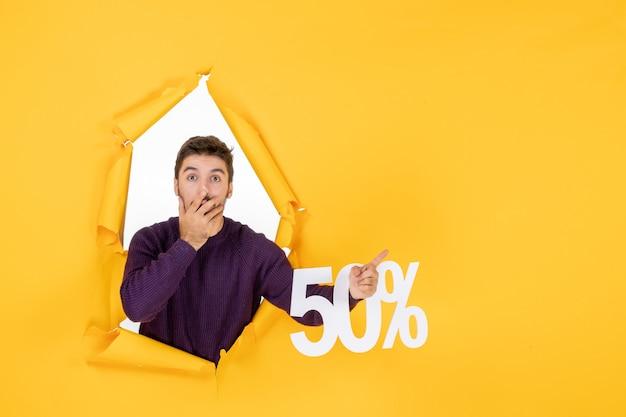 Vooraanzicht jonge man met schrijven op gele achtergrond winkelen xmas kleur cadeau verkoop vakantie foto