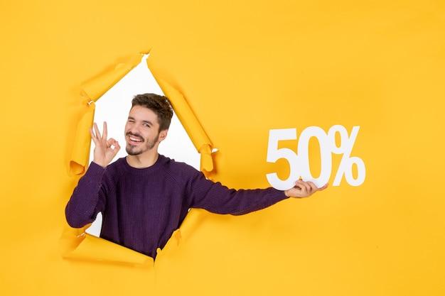 Vooraanzicht jonge man met schrijven op gele achtergrond winkelen xmas kleur geschenken verkoop vakantie foto