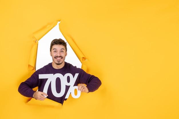 Vooraanzicht jonge man met schrijven op gele achtergrond xmas kleur winkelen cadeau foto