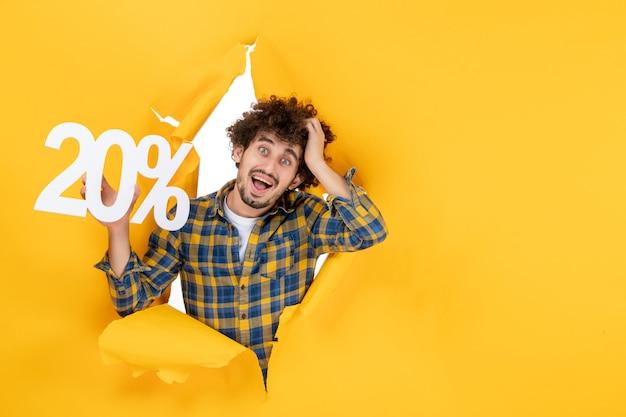 Vooraanzicht jonge man met schrijven op gele achtergrond