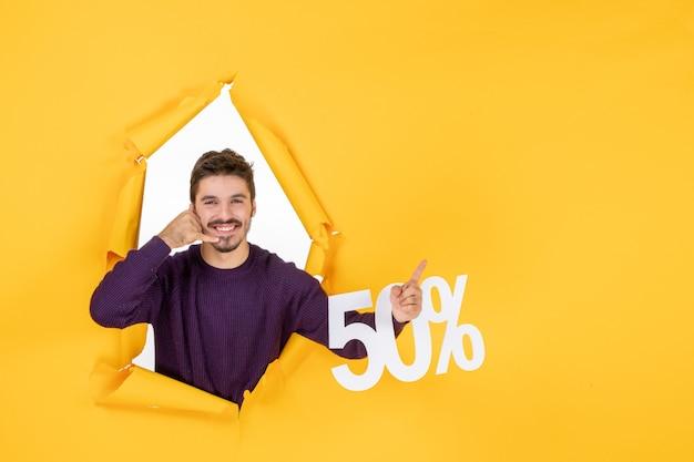 Vooraanzicht jonge man met schrijven op gele achtergrondkleur foto cadeau verkoop xmas shopping vakantie