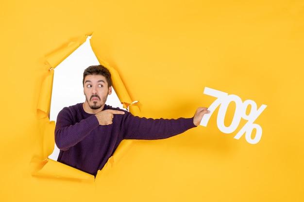 Vooraanzicht jonge man met schrijven op gele achtergrondkleur winkelen vakantie cadeau xmas foto