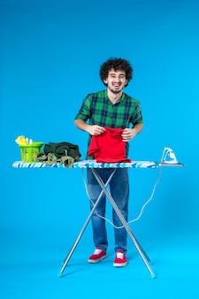Vooraanzicht jonge man met shirt op blauwe achtergrond schone wasmachine huishoudelijk werk huis kleur mens