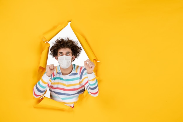 Vooraanzicht jonge man met steriel masker op gele gezondheidskleur covid coronavirus menselijke foto pandemie