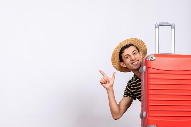 Vooraanzicht jonge man met strooien hoed achter rode koffer wijzend op iets