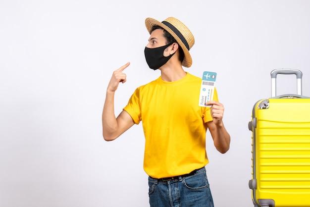 Vooraanzicht jonge man met strooien hoed en geel t-shirt staande in de buurt van gele koffer met vliegticket