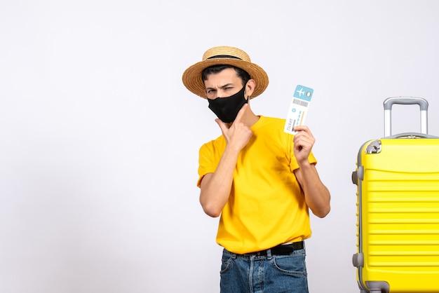 Vooraanzicht jonge man met strooien hoed en masker staande in de buurt van gele koffer met vliegticket