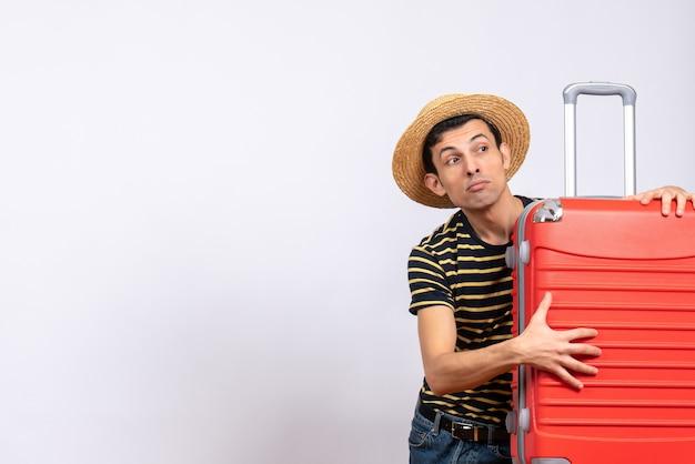 Vooraanzicht jonge man met strooien hoed met rode koffer
