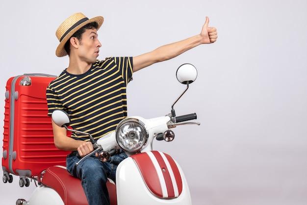 Vooraanzicht jonge man met strooien hoed op bromfiets duim opgevend