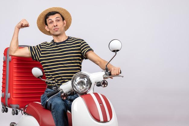 Vooraanzicht jonge man met strooien hoed op bromfiets met armspier