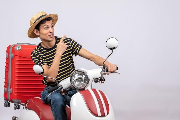 Vooraanzicht jonge man met strooien hoed op bromfiets wijzend met vinger iets