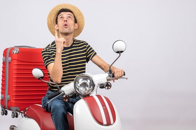 Vooraanzicht jonge man met strooien hoed op bromfiets wijzende vinger omhoog