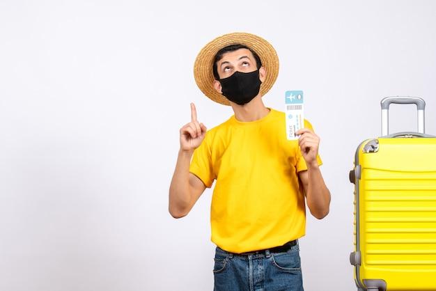 Vooraanzicht jonge man met strooien hoed staande in de buurt van gele koffer met vliegticket