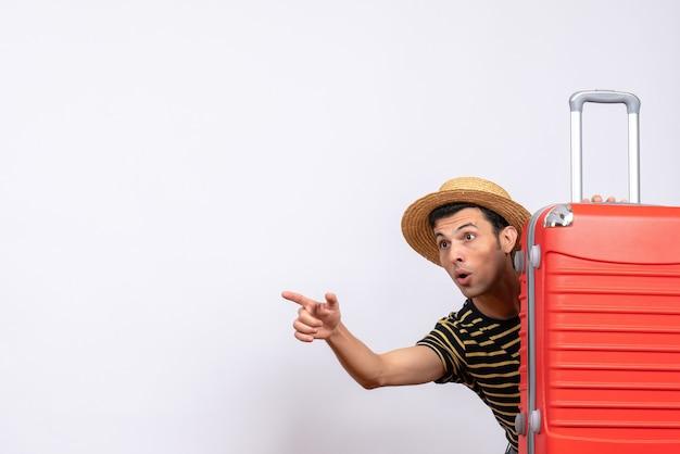 Vooraanzicht jonge man met strooien hoed verstopt achter rode koffer wijzend op iets
