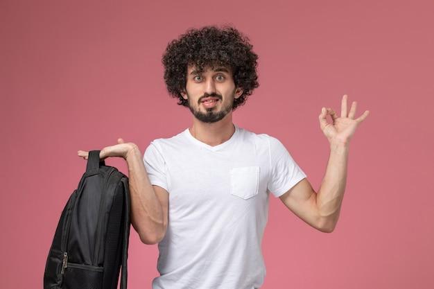 Vooraanzicht jonge man met tas en oke gebaar tonen