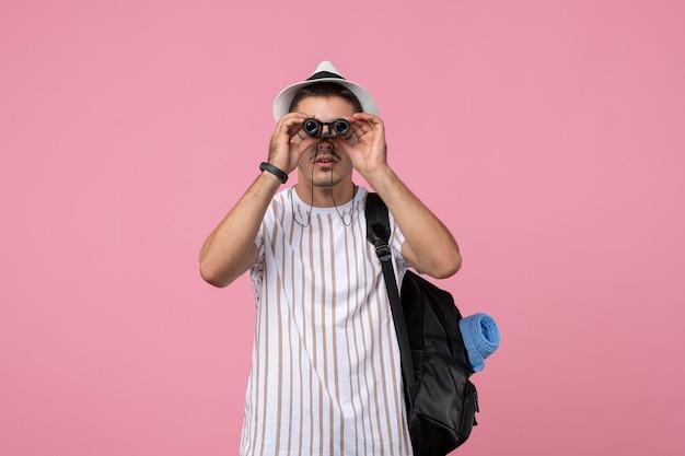 Vooraanzicht jonge man met tas en verrekijker op de roze achtergrond