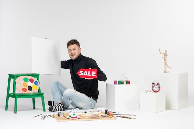 Vooraanzicht jonge man met tekening en verkoop schrijven op witte muur kleur baan tentoonstelling foto tekening kunstenaar verf kunst