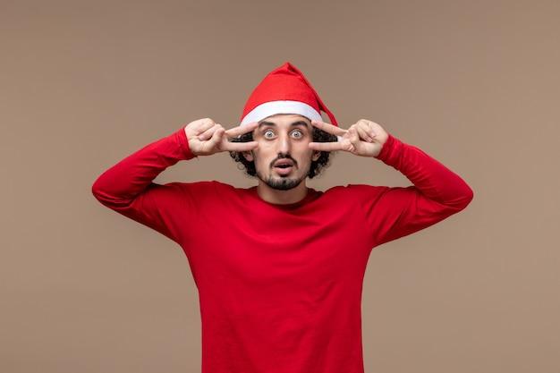 Vooraanzicht jonge man met verbaasd gezicht op donkere bruine achtergrond emotie kerstvakantie