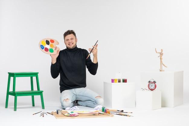 Vooraanzicht jonge man met verf en kwastje voor het tekenen op een witte muur verf kleur schilderij foto kunstenaar kunst tekenen man