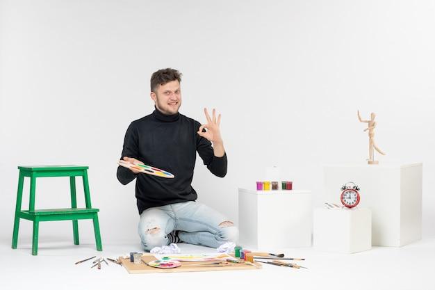 Vooraanzicht jonge man met verf en kwastje voor het tekenen op witte muurverf man kleur schilderij kunstenaar kunst tekenen foto