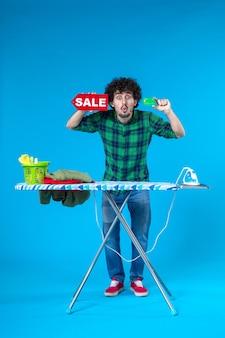 Vooraanzicht jonge man met verkoop schrijven en bankkaart op blauwe achtergrond geld wasmachine schoon winkelen huishoudelijk werk was