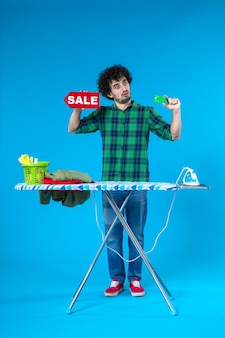 Vooraanzicht jonge man met verkoop schrijven en bankkaart op blauwe achtergrond huis geld wasmachine schoon winkelen huishoudelijk werk was