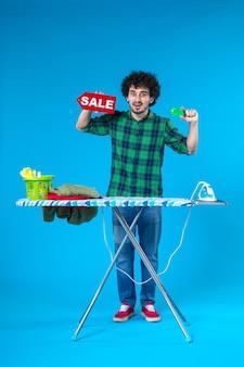 Vooraanzicht jonge man met verkoop schrijven en bankkaart op blauwe achtergrond huis geld wasmachine schoon winkelen huishoudelijk werk