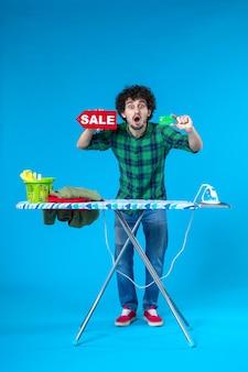 Vooraanzicht jonge man met verkoop schrijven en bankkaart op blauwe achtergrond huis geld wasmachine winkelen huishoudelijk werk was