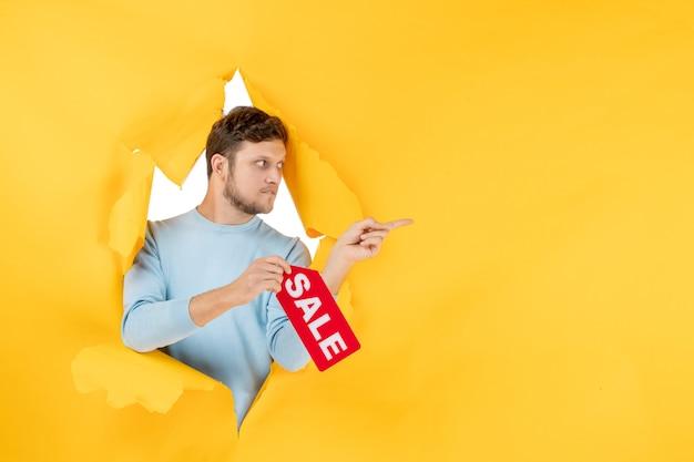 Vooraanzicht jonge man met verkoop schrijven op gele muur