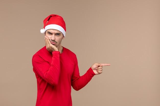 Vooraanzicht jonge man met verward gezicht op bruine achtergrond emotie kerstvakantie