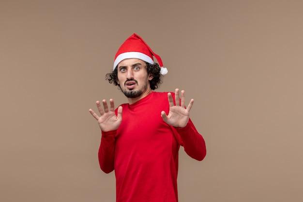 Vooraanzicht jonge man met voorzichtig gezicht op bruine achtergrond emotie kerstvakantie