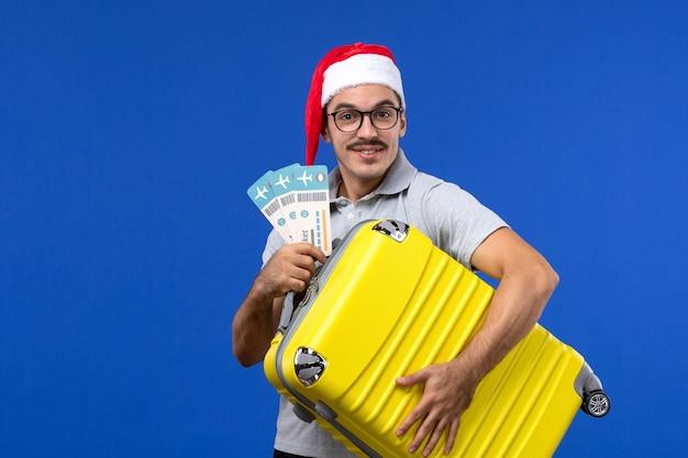 Vooraanzicht jonge man met zware tas met kaartjes op blauwe muur vlucht vakantie vliegtuig