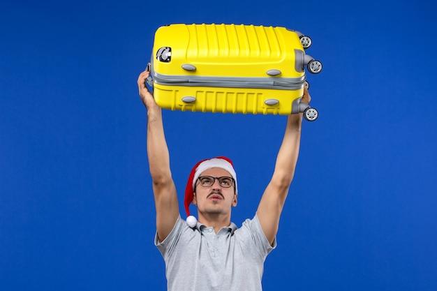 Vooraanzicht jonge man met zware tas op blauwe bureau vluchten vliegtuig vakantie