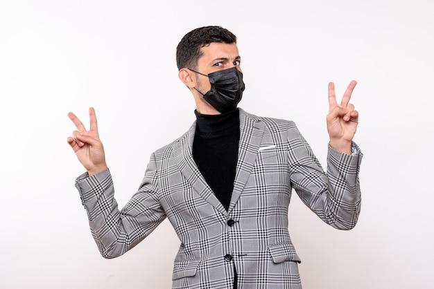 Vooraanzicht jonge man met zwart masker maken overwinning teken staande op witte geïsoleerde achtergrond