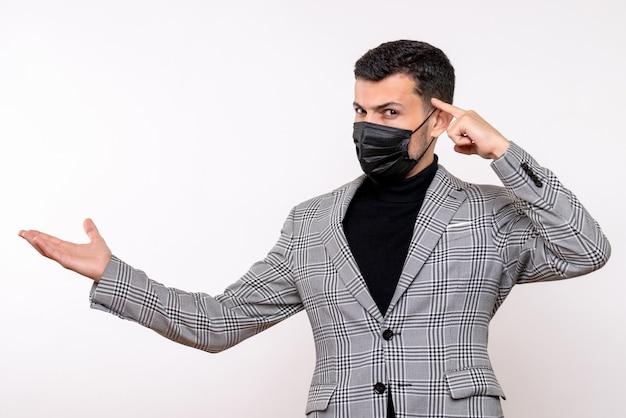 Vooraanzicht jonge man met zwart masker met iets staande op witte geïsoleerde achtergrond
