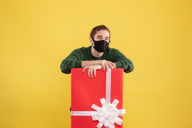 Vooraanzicht jonge man met zwart masker staande achter grote geschenkdoos op geel