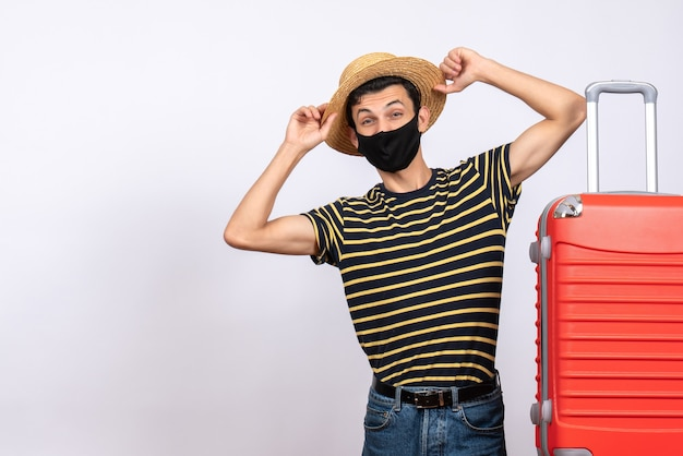 Vooraanzicht jonge man met zwart masker staande in de buurt van rode koffer met zijn hoed